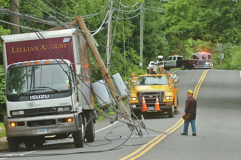 Hour photo / Erik TrautmannThe driver of a Lillian August truck backed into a utility pole, taking down the wire and transformer and creating a power outage along Wilton Road Tuesday morning. / (C)2012, The Hour Newspapers, all rights reserved