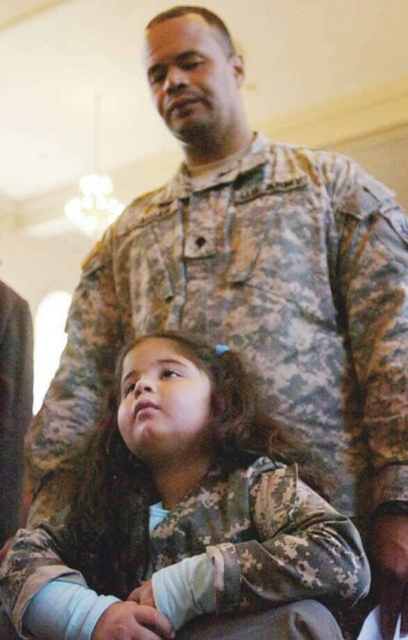 Olyvia Lizasuain watches the city's annual Veteran's Day program with her father, Army Spc. Cielo Lizasuain Friday. Hour photo / Erik Trautmann