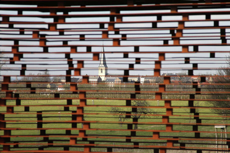 In this Feb. 20, 2013 file photo, a church is pictured through the steel layers of a see-through church on a hilltop in Borgloon, 80 km (50 miles) East of Brussels. The artistic vision of the church is made of rusty steel beams separated by gaps, and its austere beauty won it an international architecture prize. Yet the eerie desolation of the see-through installation has also turned into a reflection on the state of Roman Catholicism on a religion-weary continent where real churches, like the dozen dotting the hills of this verdant area, increasingly lose their flock and function. (AP Photo/Yves Logghe, file) / AP