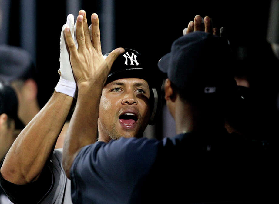 New York Yankees' Alex Rodriguez, left, gets a high-five from teammate Ivan Nova after hitting a grand slam in the eighth inning of a baseball game against the Atlanta Braves on Tuesday, June 12, 2012, in Atlanta. (AP Photo/David Goldman) / AP