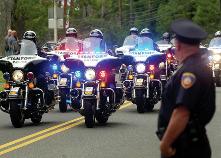 Stamford motorcycle police lead the funeral procession for Navy Petty Officer Brian Bill at St Celia Church in Stamford Friday. / (C)2011, The Hour Newspapers, all rights reserved
