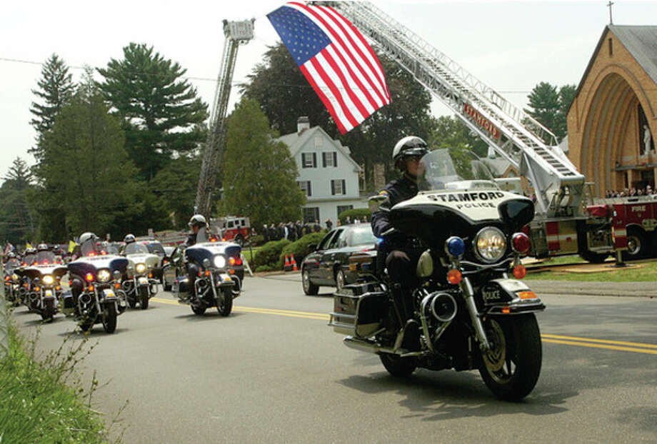 Stamford motorcycle police the lead funeral recession for Navy Chief Petty Officer Brian Bill during the funeral service for the SEAL at St. Cecelia Church Friday. / (C)2011, The Hour Newspapers, all rights reserved