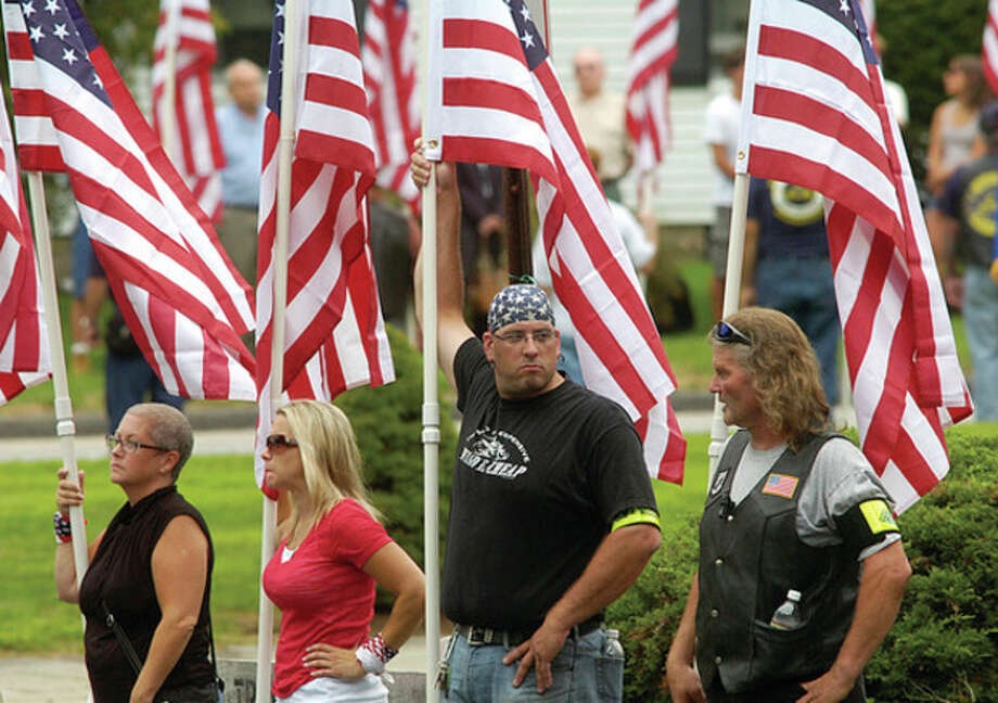 Patriot Guard Riders bear flags during the funeral service for Navy Petty Officer Brian Bill at St Celia Church in Stamford Friday. / (C)2011, The Hour Newspapers, all rights reserved