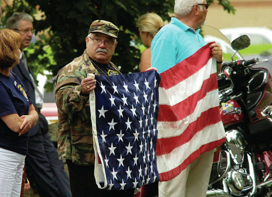 Patriots and Veterans bear flags during the funeral service for Navy Petty Officer Brian Bill at St Celia Church in Stamford Friday. / (C)2011, The Hour Newspapers, all rights reserved