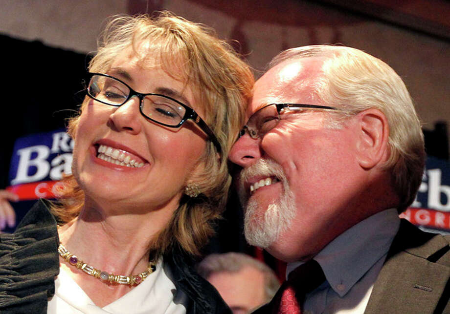 In an election to fill former Rep. Gabrielle Giffords, D-Ariz., congressional seat, Democratic candidate Ron Barber, right, celebrates a victory with Giffords, left, as he gives her a hug prior to speaking to supporters at a post election event, Tuesday, June 12, 2012, in Tucson, Ariz. Gabrielle Giffords' former district director, in a special election for the seat Giffords left in January to focus on her recovery from a gunshot wound to her head during a gunman's shooting spree a year earlier.(AP Photo/Ross D. Franklin, pool) / AP