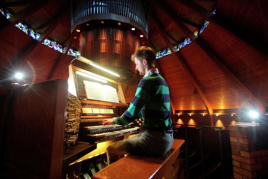 Organist Christopher Keady plays the circular pipe organ at the Agnes Flanagan Chapel Tuesday, June 12, 2012, on the campus of Lewis & Clark College, in Portland, Ore. The Agnes Flanagan Chapel is a 16-sided architectural marvel that seats 650 under stained glass windows depicting the book of Genesis. In the early 1970s, it was also a big, conical quandary. Chapels aren't really chapels unless they have an organ, and the newly-minted structure at Portland's Lewis & Clark College was in need. (AP Photo/Rick Bowmer) / AP