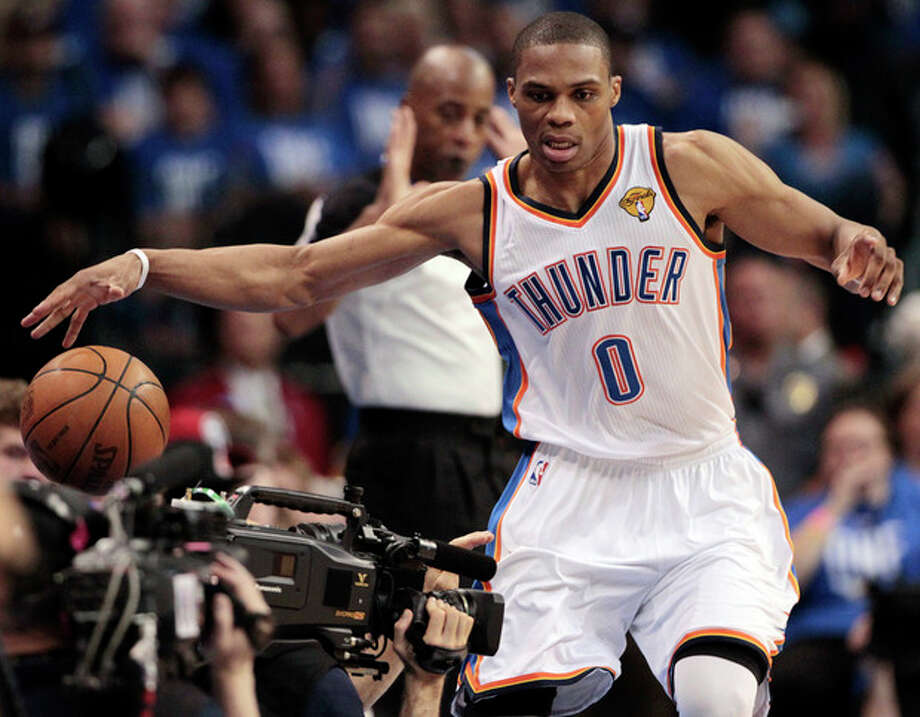 Oklahoma City Thunder point guard Russell Westbrook (0) tries to keep the ball from going out against the Miami Heat during the first half at Game 1 of the NBA finals basketball series, Tuesday, June 12, 2012, in Oklahoma City. (AP Photo/Jeff Roberson) / AP