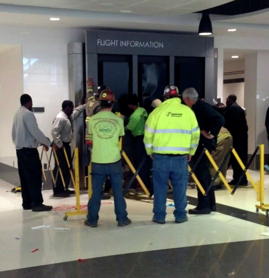 People hold up a message board sign that fell on a family killing a child and injuring the mother and two other children in the terminal at the Birmingham-Shuttlesworth International Airport in Birmingham, Ala., Friday, March 22, 2013. (AP Photo/ AL.com, Carol Robinson) MAGS OUT / AL.com