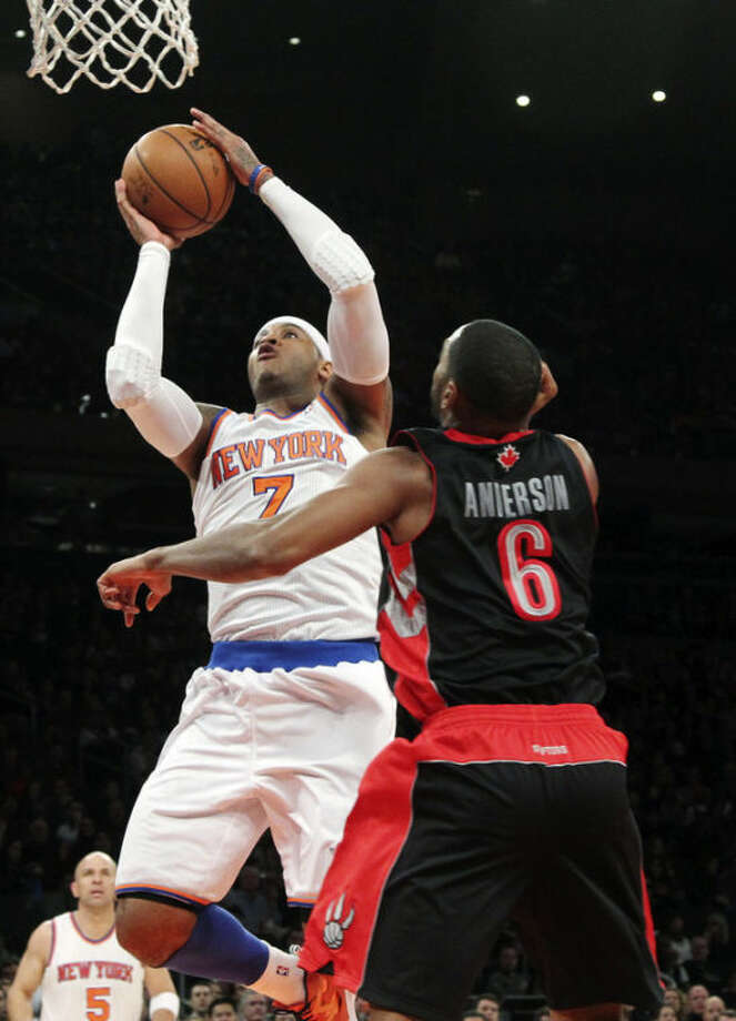 New York Knicks' Carmelo Anthony (7) goes up past Toronto Raptors' Alan Anderson (6) during the first half of an NBA basketball game, Saturday, March 23, 2013, at Madison Square Garden in New York. (AP Photo/Mary Altaffer)