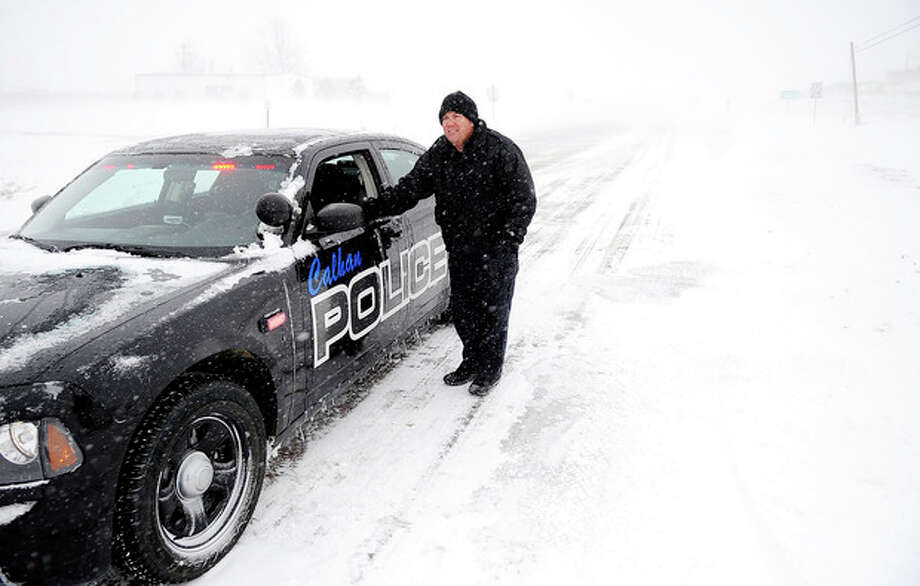 Calhan Police Sgt. Josh Morrision stands by his car as he blocks Eastbound traffic on Highway 24 outside of Calhan, Colo. as blowing snow and slick roads closed the highway Saturday, March 23, 2013. Transportation officials said Interstate 70 was closed from Denver to Colby, Kan., on Saturday. The National Weather Service said the Denver area could see up to 7 inches of snow Saturday. (AP Photo/The Colorado Springs Gazette, Michael Ciaglo) MAGS OUT / The Colorado Springs Gazettea