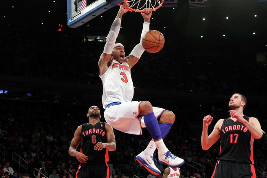 New York Knicks' Kenyon Martin (3) dunks as Toronto Raptors' Jonas Valanciunas (17) and Alan Anderson watch during the first half of an NBA basketball game, Saturday, March 23, 2013, at Madison Square Garden in New York. (AP Photo/Mary Altaffer) / AP