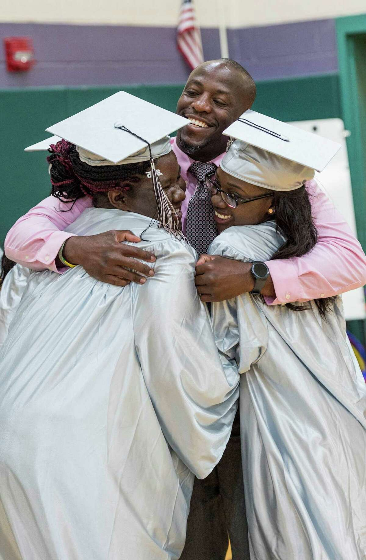 Former Bridge Academy teacher Migel Pickering greets a couple of his old students Kimone Heywood and Brittney Williams at the Bridge Academy Nineteenth Annual Graduation held at the Thurgood Marshall Middle School, Bridgeport, CT on Tuesday, June 14, 2016.