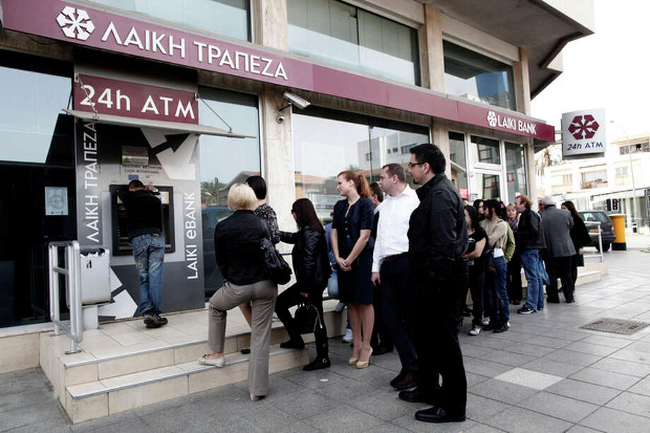 People queue at an ATM outside a closed Laiki Bank branch in capital Nicosia, Cyprus, Thursday, March 21, 2013. The European Central Bank says it will keep emergency aid for Cyprus' troubled banks in place at least until Monday but will have to cut it off after that unless an international rescue program is drawn up. (AP Photo/Petros Giannakouris) / AP