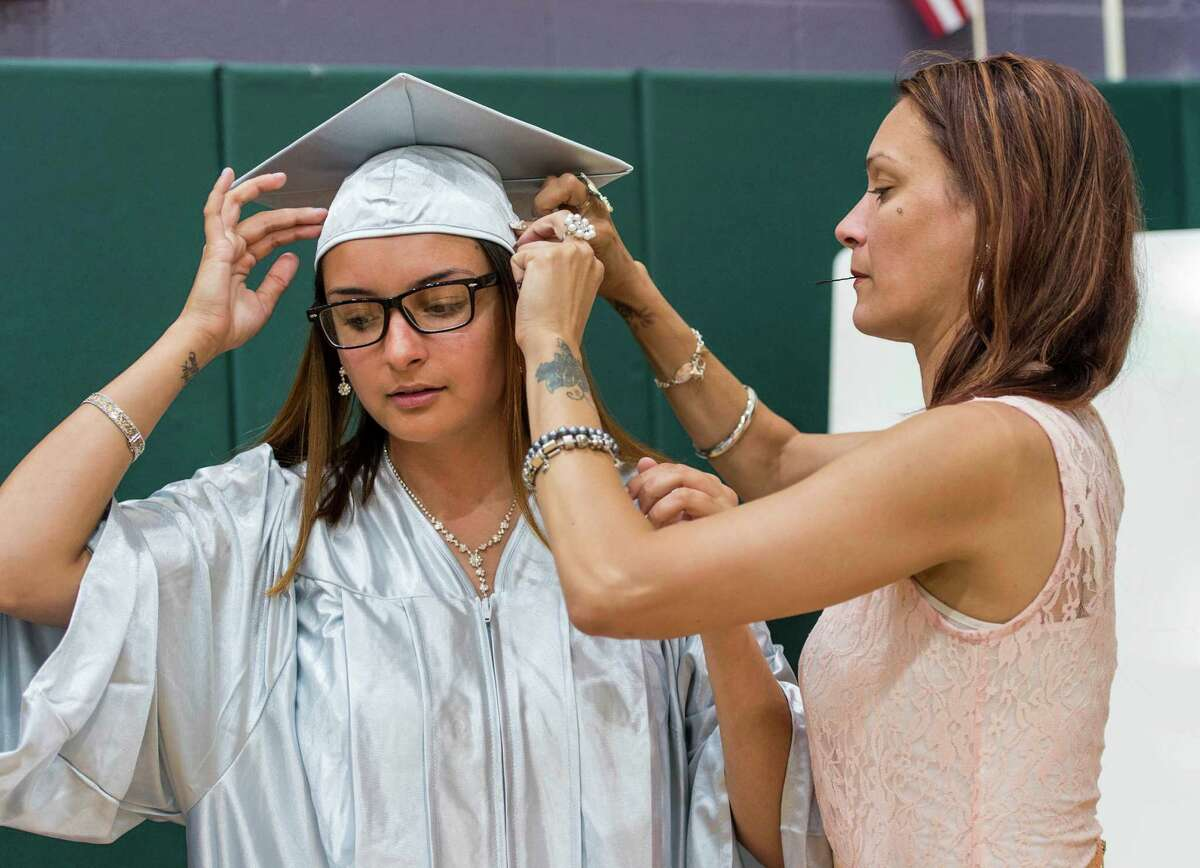 Jessy Toro (right) helps her daughter Elisa Martinez with her cap prior to the Bridge Academy Nineteenth Annual Graduation held at the Thurgood Marshall Middle School, Bridgeport, CT on Tuesday, June 14, 2016.