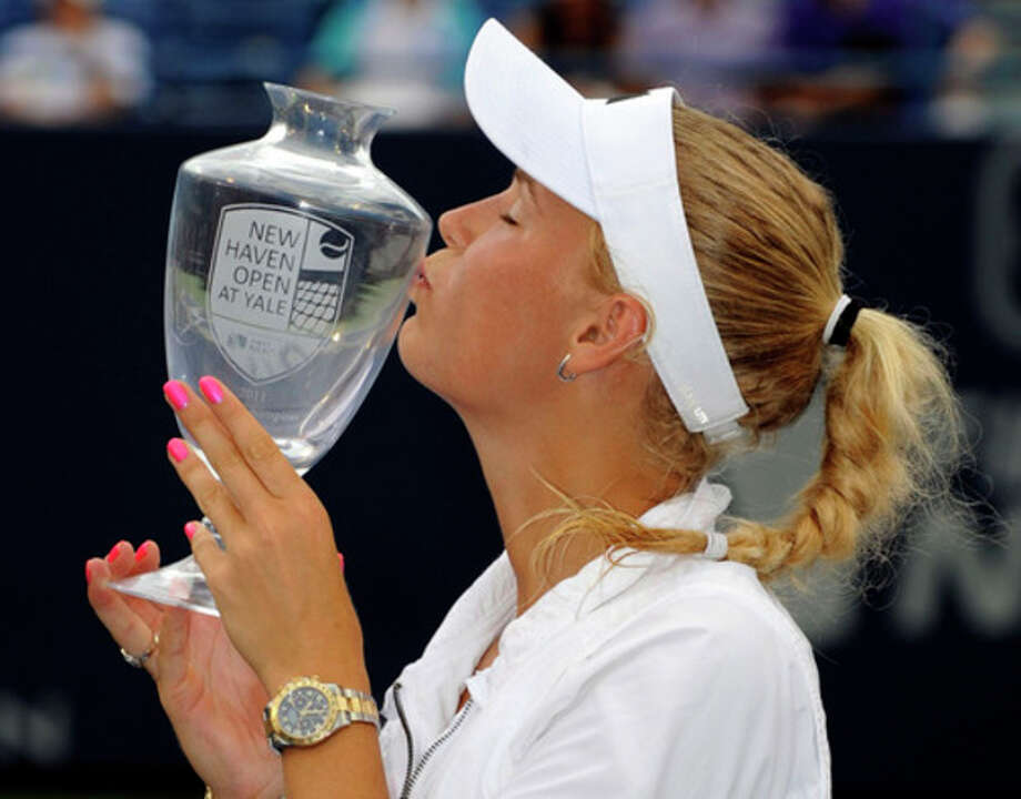 Caroline Wozniacki, of Denmark, celebrates with her trophy after defeating Petra Cetkovska, of the Czech Republic, 6-4, 6-1 in the finals of the New Haven Open tennis tournament in New Haven, Conn., on Saturday, Aug. 27, 2011. (AP Photo/Fred Beckham) / FR153656 AP