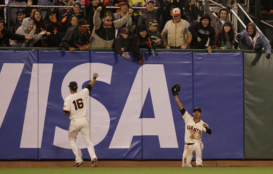San Francisco Giants center fielder Gregor Blanco, right, celebrates with left fielder Angel Pagan (16) after catching a fly ball hit by Houston Astros' Jordan Schafer during the seventh inning of a baseball game in San Francisco, Wednesday, June 13, 2012. Giants pitcher Matt Cain pitched a perfect game. The Giants won 10-0. (AP Photo/Jeff Chiu) / AP