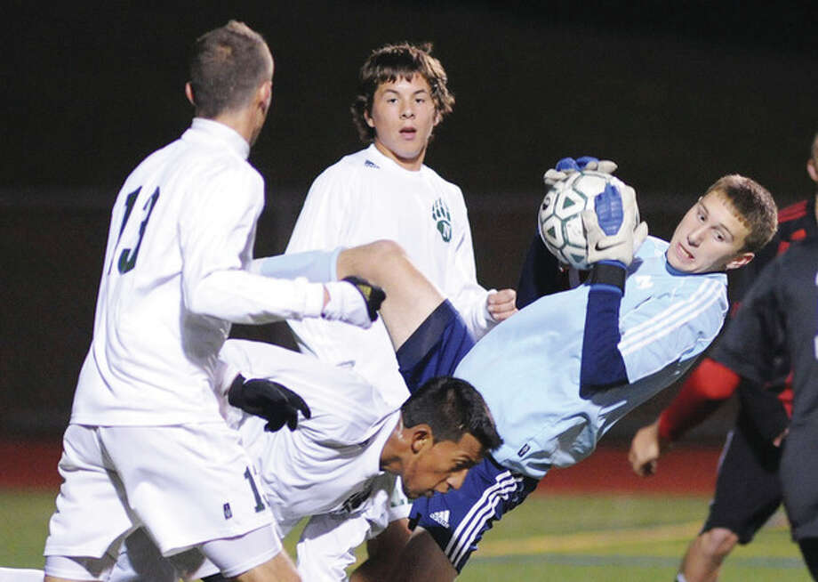 Hour Photo/John Nash New Canaan goalkeeper Scott Levene, right, gets upended on a corner kick as he collects the ball while surrounded by Norwalk's Andrew Melitsanopoulous, left, Santiago Muriel, bottom, and Chris Miklave during the second half of Friday night's FCIAC boys soccer quarterfinal at Testa Field. The Rams won, 2-1