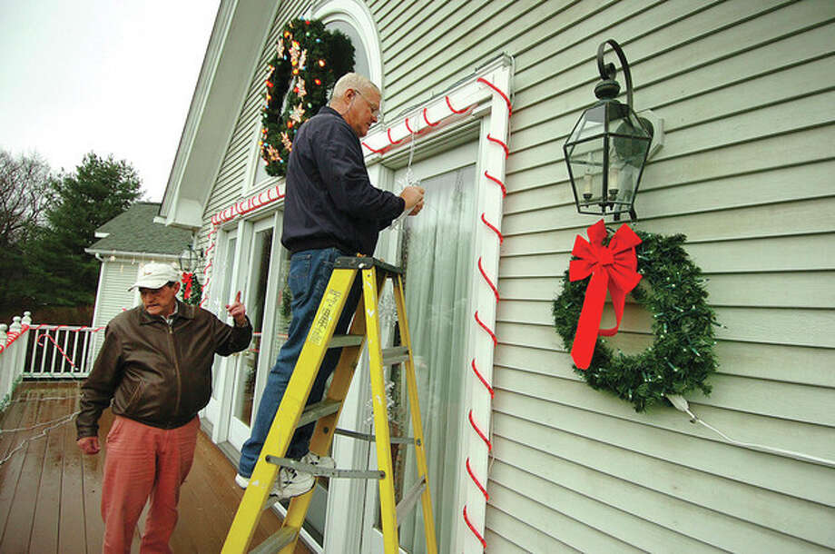 Hour Photo/ Alex von Kleydorff. Walter Schalk helps Charlie Micha with hanging lights on the deck at his Wilton home. / 2011 The Hour Newspapers