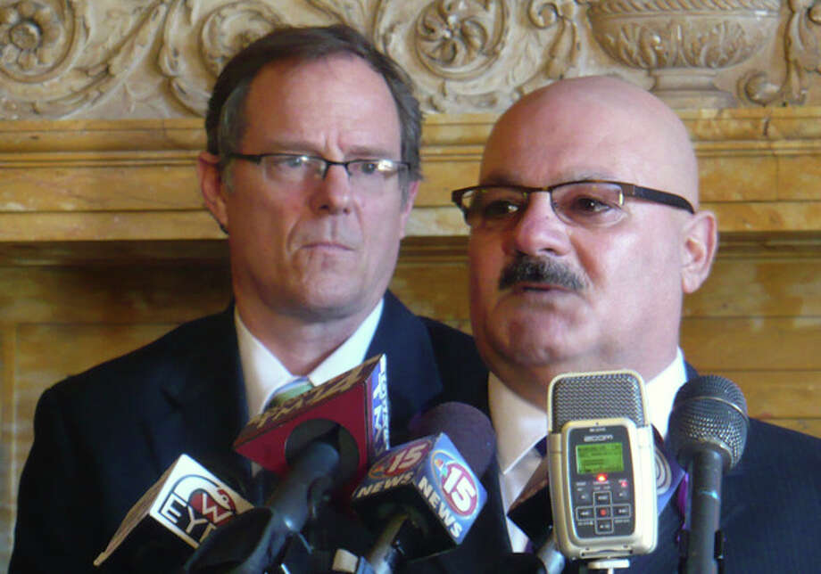 Elvin Daniel, right, whose sister Zina was killed by her husband last October at a Brookfield spa, said the tragedy could have been avoided if the law required background checks for private transactions of guns during a news conference with law enforcement officials and some Democratic lawmakers, including Rep. Jon Richards, left, Thursday, March 21, in Madison, Wis. Democrats have a new proposal that would make it illegal to purchase or transfer guns without running background checks. (AP Photo/Kevin Wang) / AP