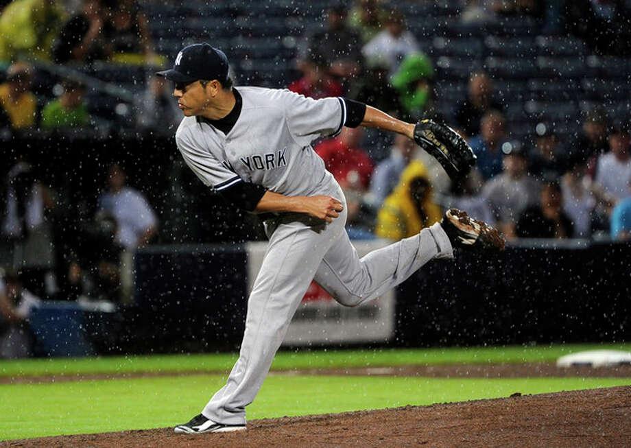 New York Yankees pitcher Hiroki Kuroda works the mound in the rain against the Atlanta Braves during the fourth inning of a baseball game, on Wednesday, June 13, 2012, in Atlanta. (AP Photo/John Amis) / FR69715 AP