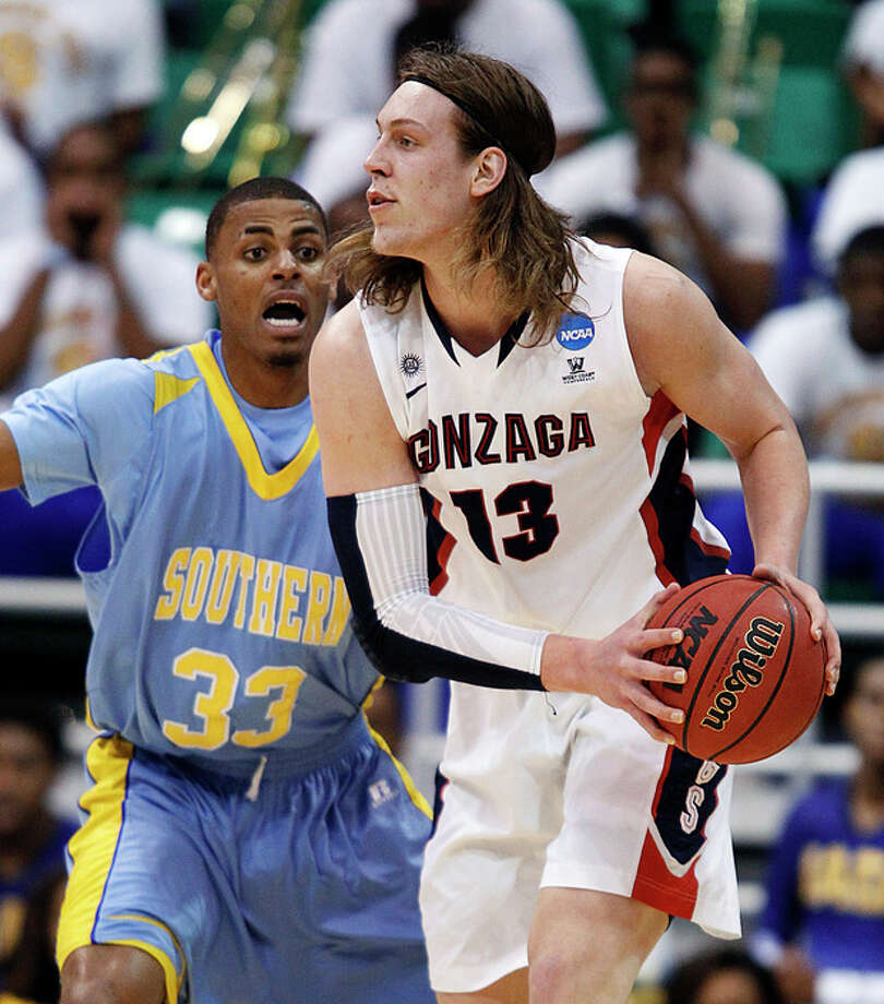 Gonzaga's Gonzaga's Kelly Olynyk, right, looks to pass as Southern University's Malcolm Miller defends in the first half during a second-round game in the NCAA college basketball tournament in Salt Lake City, Thursday, March 21, 2013. (AP Photo/George Frey) / FR10102 AP