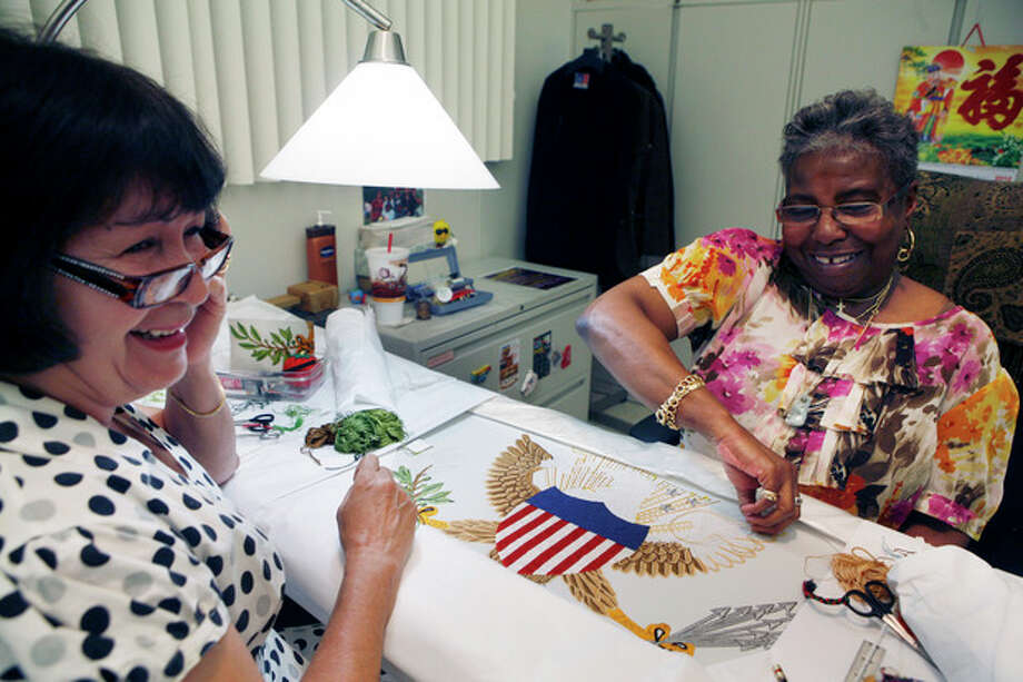 In this Tuesday, June 12 photo, Nereida Rivera, left and Christine Upchurch, both of Philadelphia, hand embroider a vice presidential flag at the Defense Logistics Agency in Philadelphia. The vice presidential flag takes the two fabric workers 35 days to complete. About 10 miles from the house where Betsy Ross is believed to have sewn the first U.S. flag, Upchruch and Rivera are two of about a dozen seamstresses at a military supply operation who are the sole producers of the hand-stitched vice presidential banners. (AP Photo/Brynn Anderson) / AP