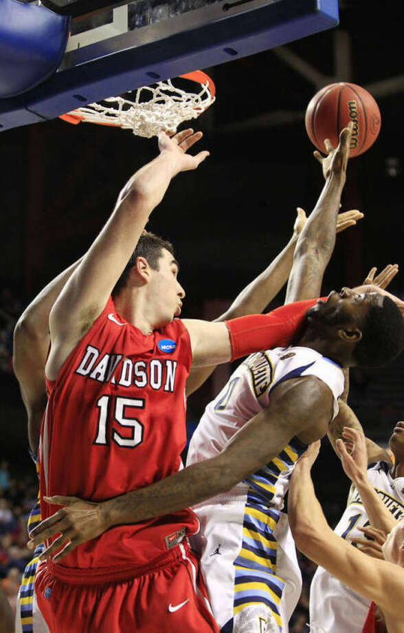 Davidson forward Jake Cohen (15) and Marquette forward Jamil Wilson (0) battle for a rebound during the first half of a second-round game in the NCAA college basketball tournament Thursday, March 21, 2013, in Lexington, Ky. (AP Photo/James Crisp)