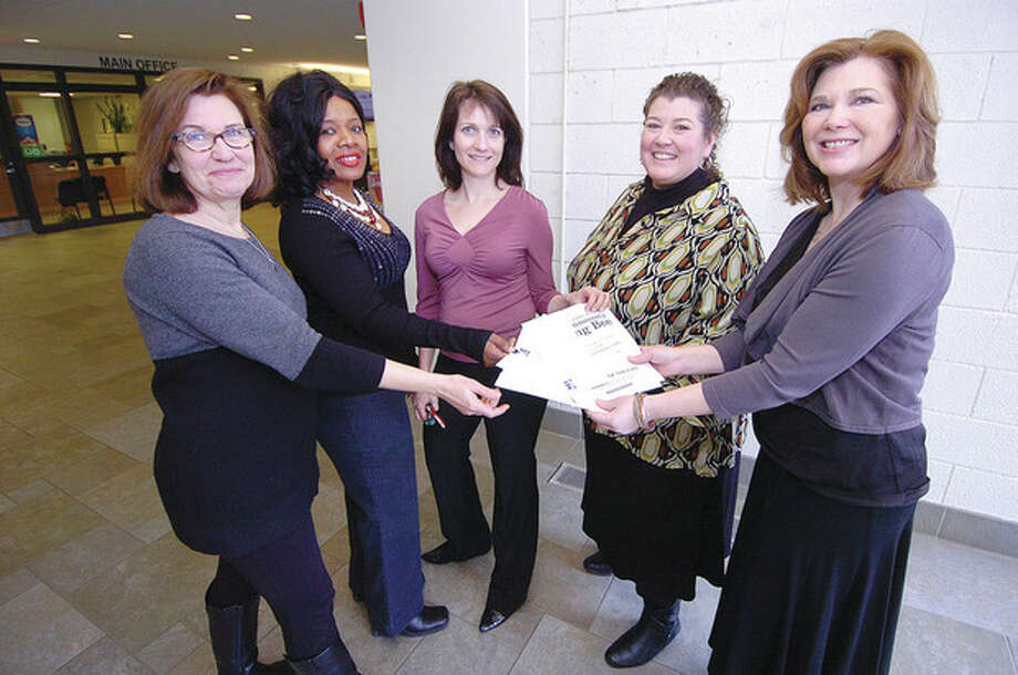 Hour Photo/Alex von KleydorffFrom the left, Norwalk High School teachers Katy Milne, Willetta Payton, Juliette Shimkets, accept mini grants form Norwalk Education Foundation Board Member Liz Reid and NEF Executive Director Glori Tenofsky. / 2013 The Hour Newspapers