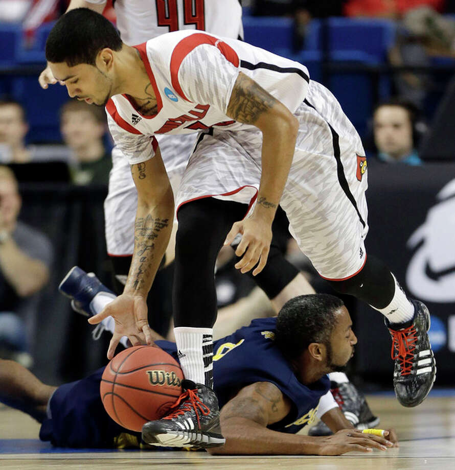 Louisville guard Peyton Siva (3) scoops the ball up after stealing it from North Carolina A&T forward DaMetrius Upchurch (4) during the second half of a second-round game in the NCAA college basketball tournament, Thursday, March 21, 2013, in Lexington, Ky. Louisville won 79-48. (AP Photo/John Bazemore) / AP
