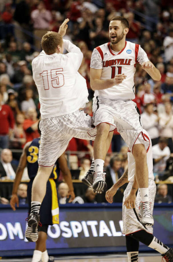 Louisville's Luke Hancock (11) and Tim Henderson (15) celebrate during the second half of a second-round game in the NCAA college basketball tournament against the North Carolina A&T Thursday, March 21, 2013, in Lexington, Ky. (AP Photo/John Bazemore)
