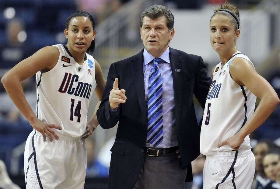 Connecticut head coach Geno Auriemma, center, speaks with Bria Hartley, left, and Caroline Doty during the first half of an NCAA tournament second-round college basketball game against Kansas State in Bridgeport, Conn., Monday, March 19, 2012. Connecticut won 72-26. (AP Photo/Jessica Hill)