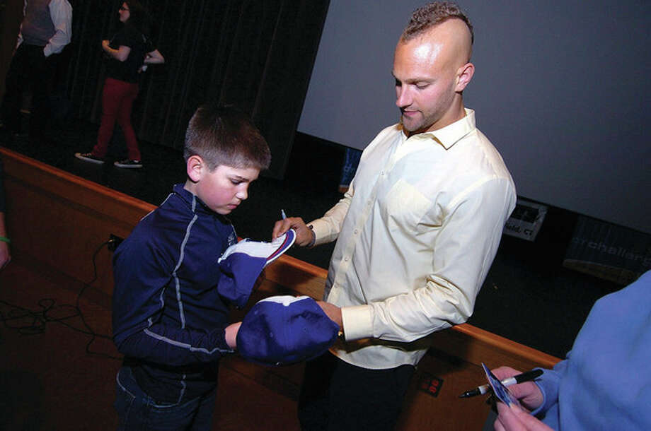 Hour photo/Alex von KleydorffNew York Giants linebacker Mark Herzlich signs some CT Challenge hats for 10-year-old cancer survivor Justin Ordway, who came from Southbury with his family to hear the player's talk. / 2013 The Hour Newspapers