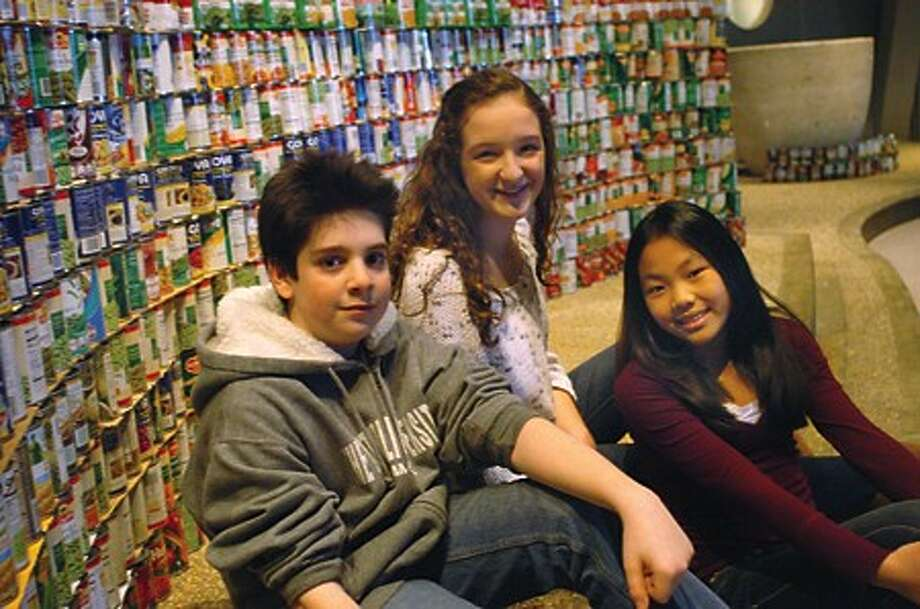 Thomas Chiappetta 12, Emily Rybnick 15 and Olivia DiMarco 13 at the St. Phillip Church in Norwalk with some of the collected cans donated for it''s 30- Hour Famine event to help families in need. hour photo/matthew vinci