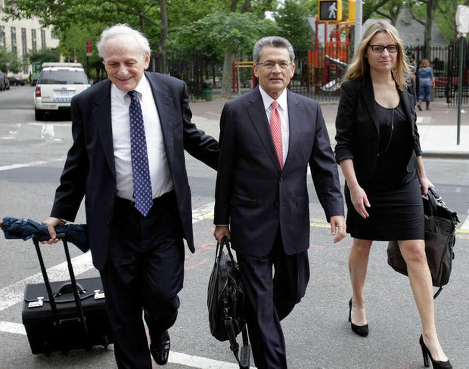 Rajat Gupta, center, and members of his legal team arrive at court in New York, Tuesday, June 12, 2012. Gupta is pleading not guilty to charges he passed secrets he learned from Goldman's board in fall 2008 to a billionaire hedge fund founder who used the information to make millions of dollars. (AP Photo/Seth Wenig) / AP