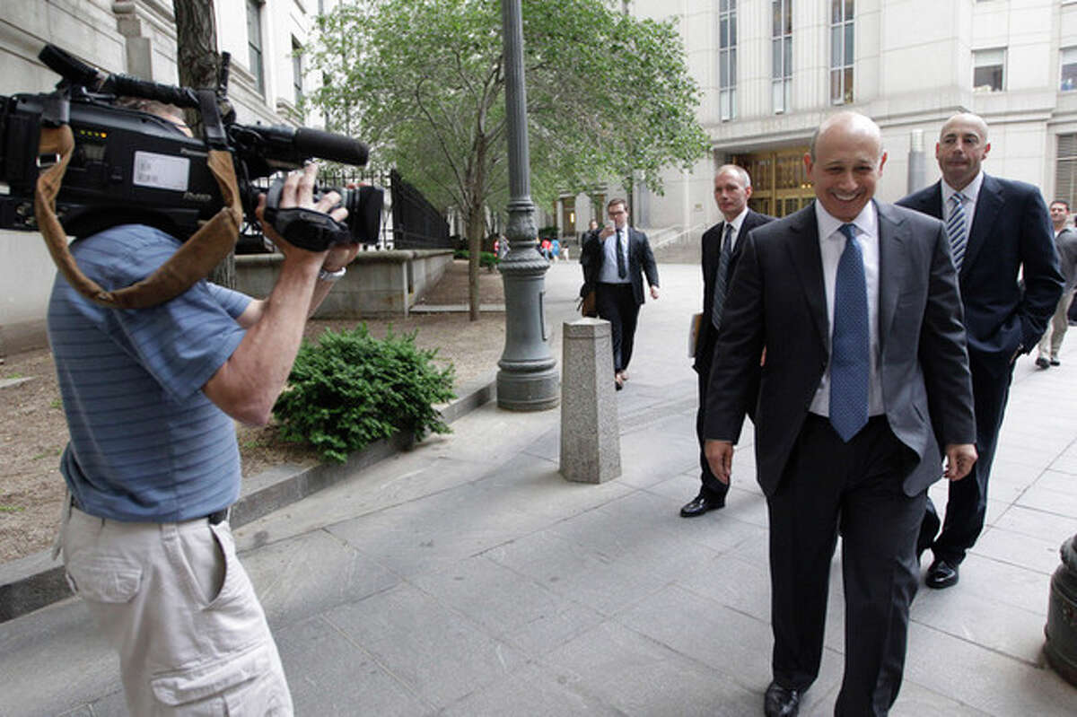 Goldman Sachs chairman and chief executive officer Lloyd Blankfein, right, is filmed by a television photographers as he leaves Federal court, Thursday, June 7, 2012 in New York. Blankfein testified at the New York insider trading trial of a former Goldman board member Rajat Gupta. (AP Photo/Mary Altaffer)