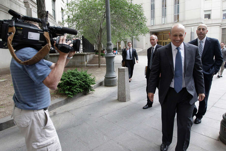 Goldman Sachs chairman and chief executive officer Lloyd Blankfein, right, is filmed by a television photographers as he leaves Federal court, Thursday, June 7, 2012 in New York. Blankfein testified at the New York insider trading trial of a former Goldman board member Rajat Gupta. (AP Photo/Mary Altaffer) / AP