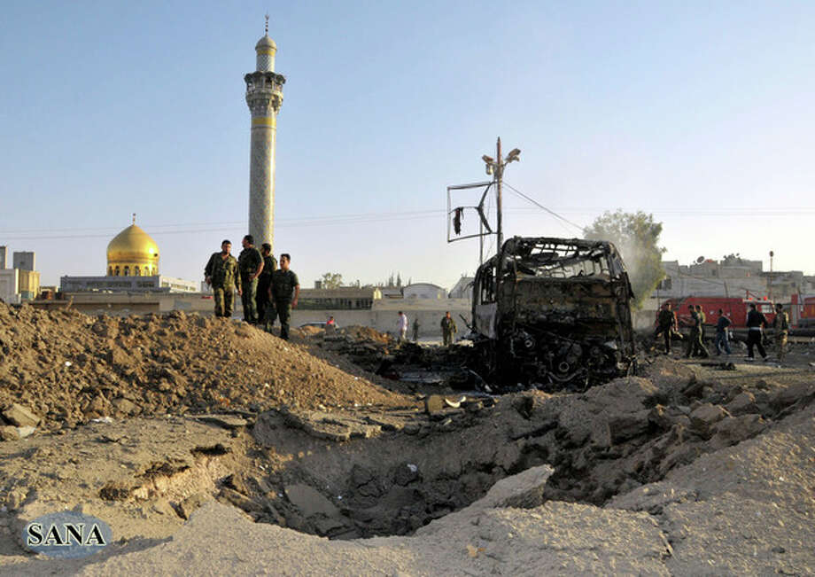 In this photo released by the Syrian official news agency SANA, Syrian soldiers stand at the explosion site where a car bomb exploded near the shrine of Sayyida Zeinab, seen in the background, suburb of Damascus, Syria, Thursday, June 14, 2012. A car bomb exploded Thursday in a Damascus suburb that is home to a popular Shiite Muslim shrine, wounding at least two people, Syria's state-run news agency SANA reported, while activists said regime troops continued shelling rebellious areas in central Homs province. (AP Photo/SANA) / SANA