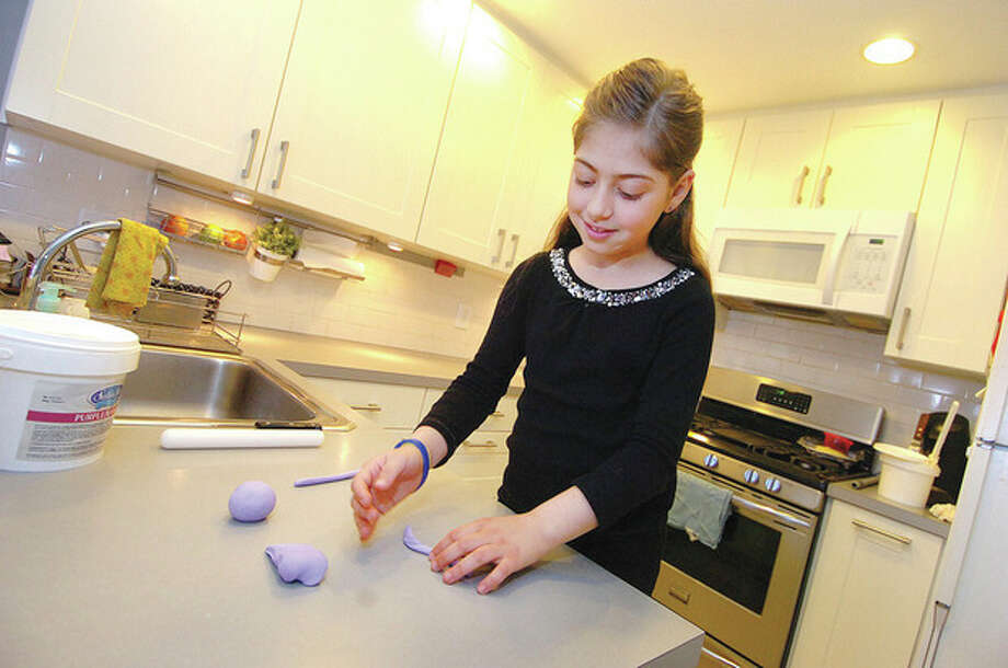 Hour photo / Alex von KleydorffIsabella Papadopoulos, 8, rolls out Fondant Sugar Dough to show how decorations were made for her award winning cake entry. / 2013 The Hour Newspapers
