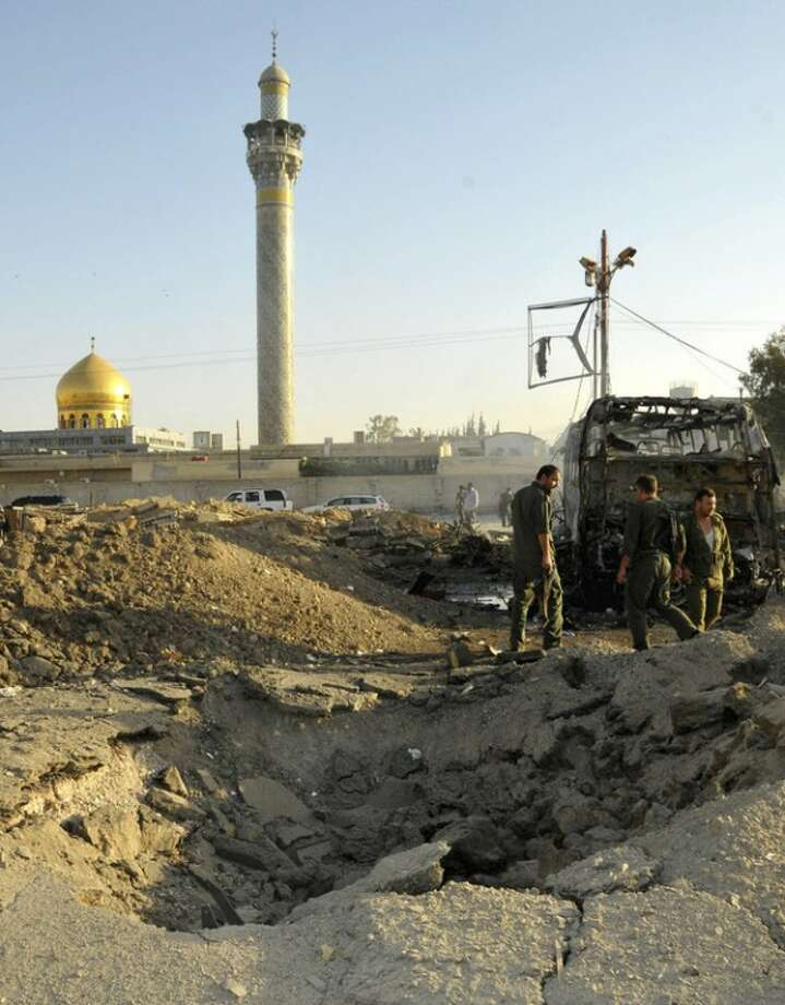 In this photo released by the Syrian official news agency SANA, Syrian soldiers stand at the explosion site where a car bomb exploded near the shrine of Sayyida Zeinab, seen in the background, a suburb of Damascus, Syria, Thursday, June 14, 2012. A car bomb exploded Thursday in a Damascus suburb that is home to a popular Shiite Muslim shrine, wounding at least two people, Syria's state-run news agency SANA reported, while activists said regime troops continued shelling rebellious areas in central Homs province. (AP Photo/SANA)