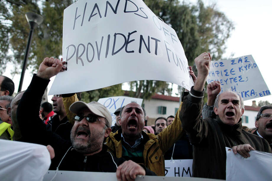 "Bank employees protest outside the ministry of finance on Saturday, March 23, 2013. Thousands of bank employees took part in a protest that ended outside the Cypriot parliament. Politicians in Cyprus were racing Saturday to complete an alternative plan raising funds necessary for the country to qualify for an international bailout, with a potential bankruptcy just three days away. Banner at right reads: ""Who voted for you members of parliament? The Troika?"" (AP Photo/Petros Giannakouris) / AP"