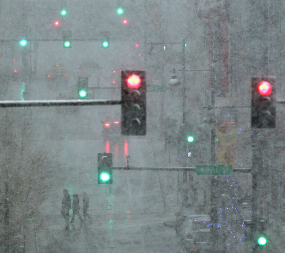Pedestrians are shrouded in heavy snow as they cross a downtown street on Saturday, March 23, 2013, in Kansas City, Mo. A winter storm warning is in effect for the area. (AP Photo/Charlie Riedel) / AP