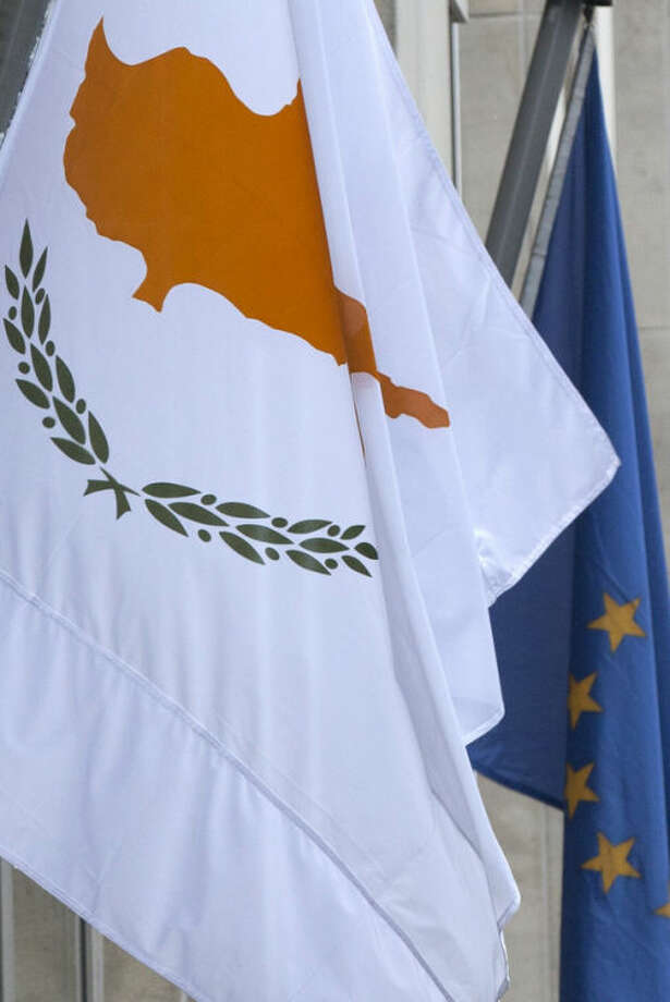 The Cypriot, left, and EU flag are seen at the Cypriot delegation building in Brussels on Sunday, March 24, 2013. The EU says a top official will chair a high-level meeting on Cyprus in a last-ditch effort to seal a deal before finance ministers decide whether the island nation gets a 10 billion euro bailout loan to save it from bankruptcy. (AP Photo/Virginia Mayo)