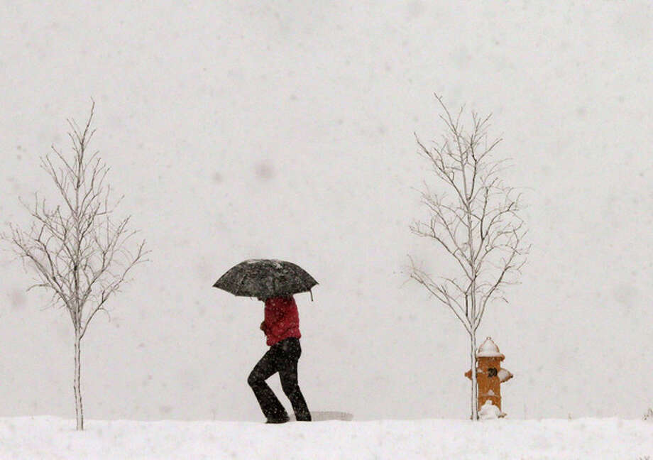 A person walks along Jayhawk Boulevard with an umbrella as snow from a winter storm begins to fall in Lawrence, Kan., Saturday, March 23, 2013. (AP Photo/Orlin Wagner) / AP