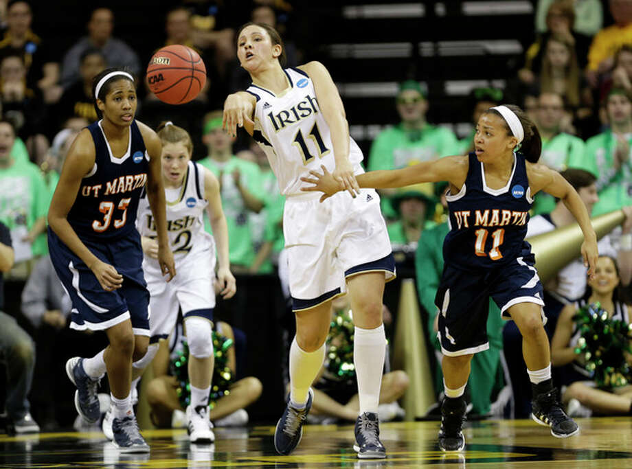 Notre Dame forward Natalie Achonwa, center, passes between Tennessee Martin forward Rickiesha Bryant, left, and guard Heather Butler, right, during the first half of a first-round game in the women's NCAA college basketball tournament on Sunday, March 24, 2013, in Iowa City, Iowa. (AP Photo/Charlie Neibergall) / AP