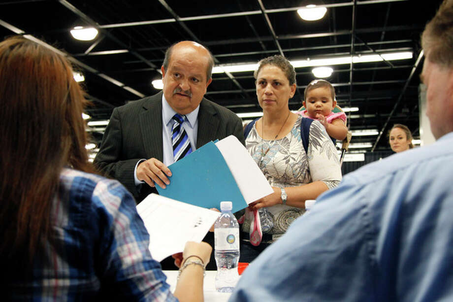 In this June 13, 2012 photo, Jose Canales, left, talks to a recruiter as he is accompanied by his wife, Magdel, and daughter Alexamarie at a job fair expo in Anaheim, Calif. More Americans sought unemployment aid last week, suggesting hiring remains sluggish. The Labor Department said Thursday June 14, 2012 that weekly unemployment benefit applications rose 6,000 to a seasonally adjusted 386,000, an increase from an upwardly revised 380,000 the previous week. (AP Photo/Jae C. Hong) / AP