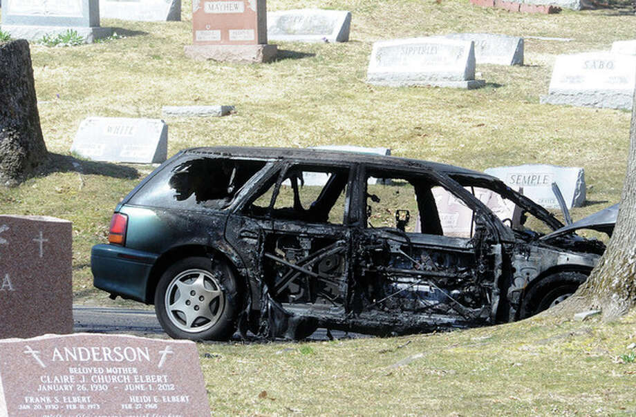 Hour photo / Matthew VinciThe remains of a car fire Sunday morning in the Riverside Cemetery in Norwalk.