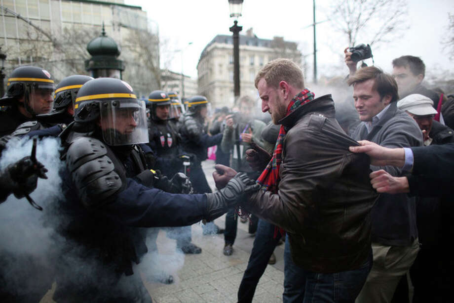 "Protestors clash with riot police officers during an anti gay marriage and gay adoption demonstration, in Paris, Sunday, March. 24, 2013. Thousands of French conservatives, families and activists have converged on the capital to try to stop the country from allowing same-sex couples to marry and adopt children. The lower house of France's parliament approved the ""marriage for everyone"" bill last month with a large majority, and it's facing a vote in the Senate next month. Both houses are dominated by French President Francois Hollande's Socialist Party and its allies. (AP Photo/Thibault Camus) / AP"