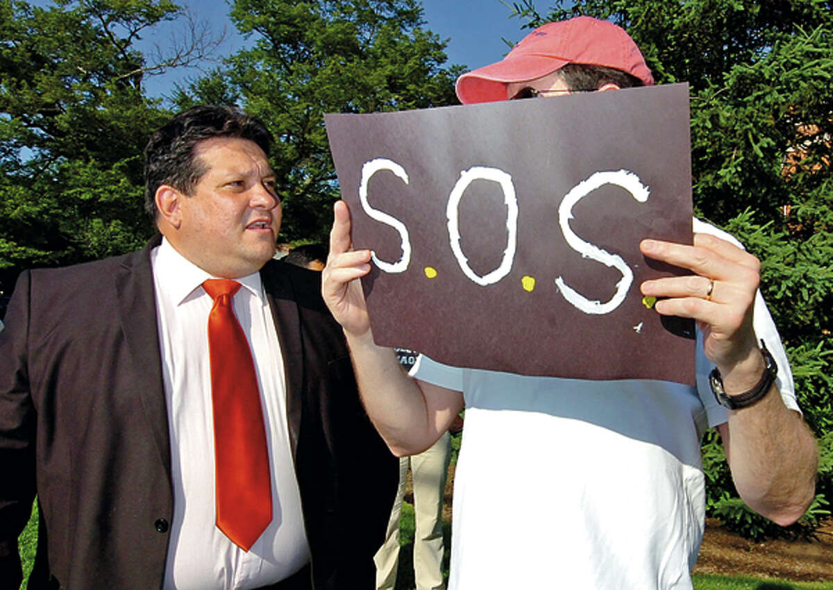 School Board chairman Jack Chiaramonte talks to protesters as they rally outside city hall addressing the budget shortfall ahead of the Common Council Finance / Claims Committee meeting Thursday. Hour photo / Erik Trautmann