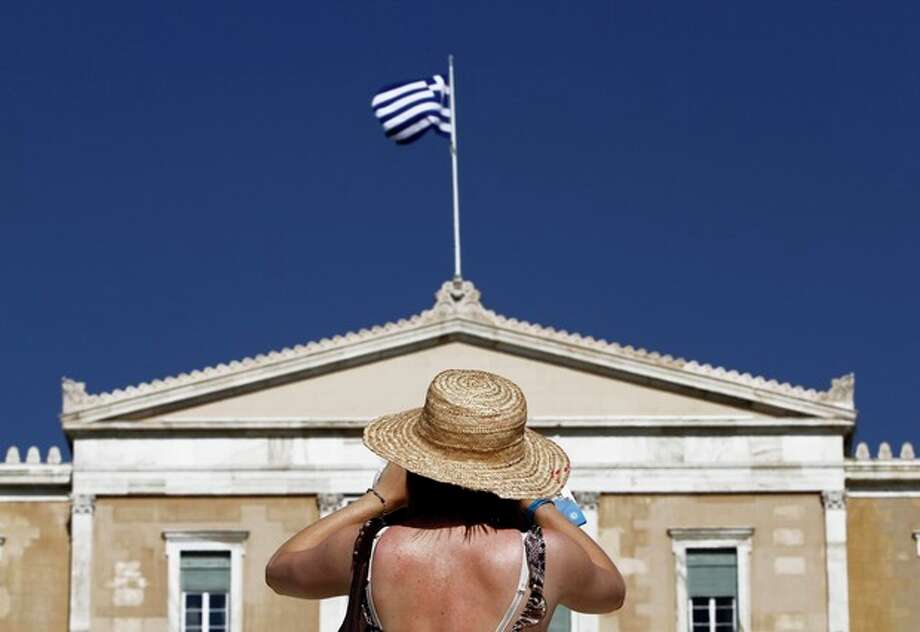 FILE- In this June 14, 2012 file photo, a tourist takes photos of the Parliament in Syntagma square in central Athens. Bankers, governments and investors are starting to prepare for Greece to drop the euro currency, a move that could spread turmoil throughout the global financial system. A Greek election on Sunday, June 16, 2012 will go a long way toward determining whether it happens. (AP Photo/Petros Karadjias, File) / AP2012