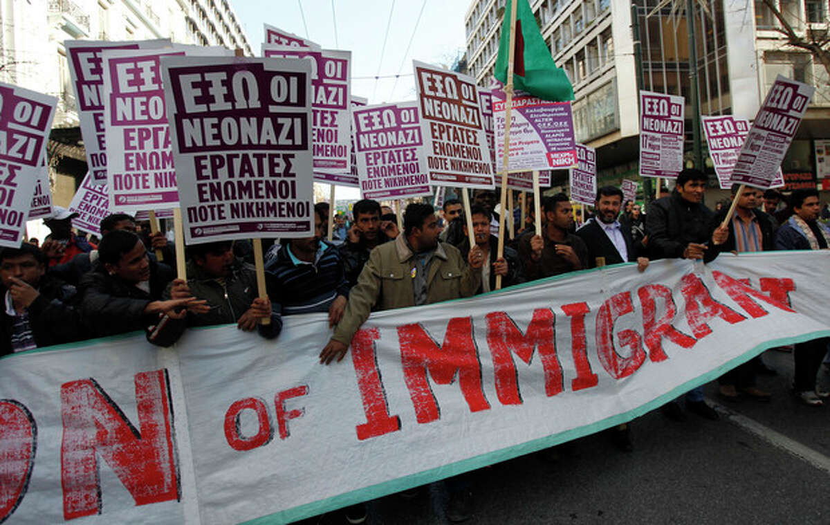 FILE - In this March 17 2012, file photo, immigrants holding placards that read